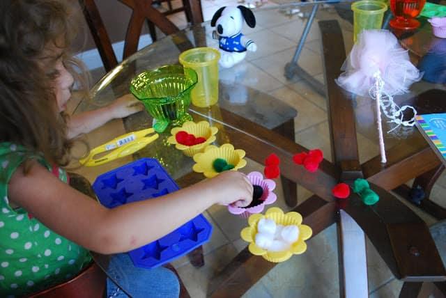 child sorting colored pom poms