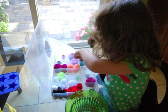 child sorting pom poms