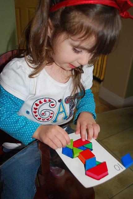 child playing with pattern blocks