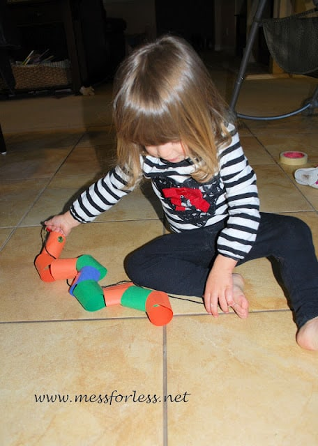 child playing with paper snake