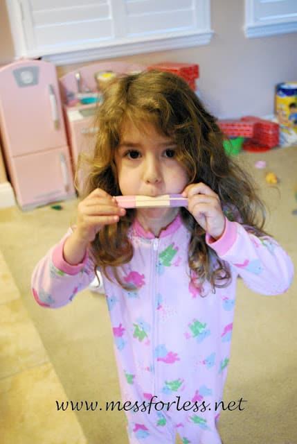 child playing homemade harmonica
