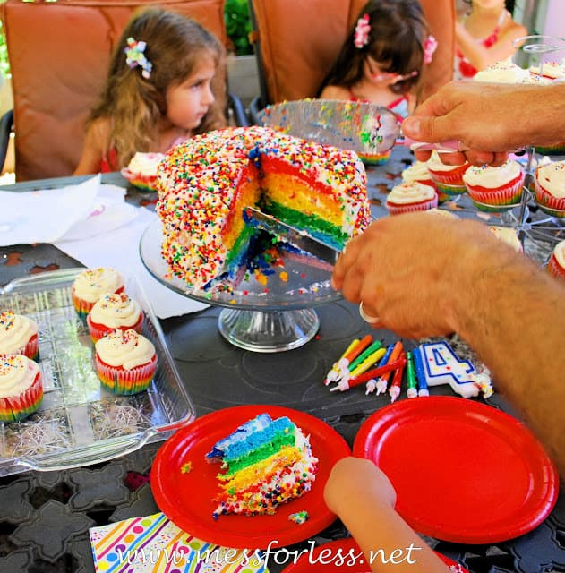 cutting a rainbow cake