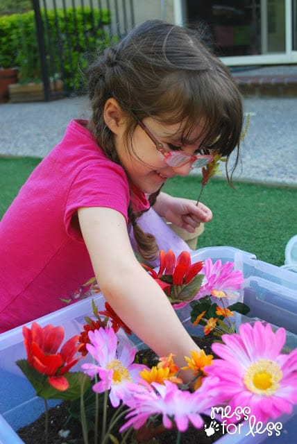 child working in a garden sensory bin