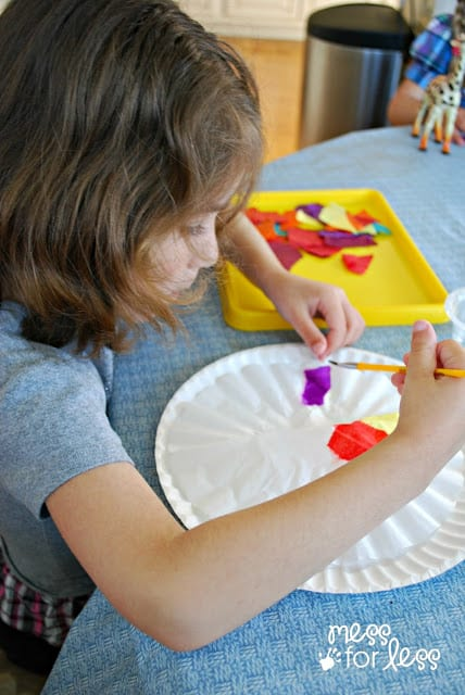 child painting with tissue paper and a coffee filter