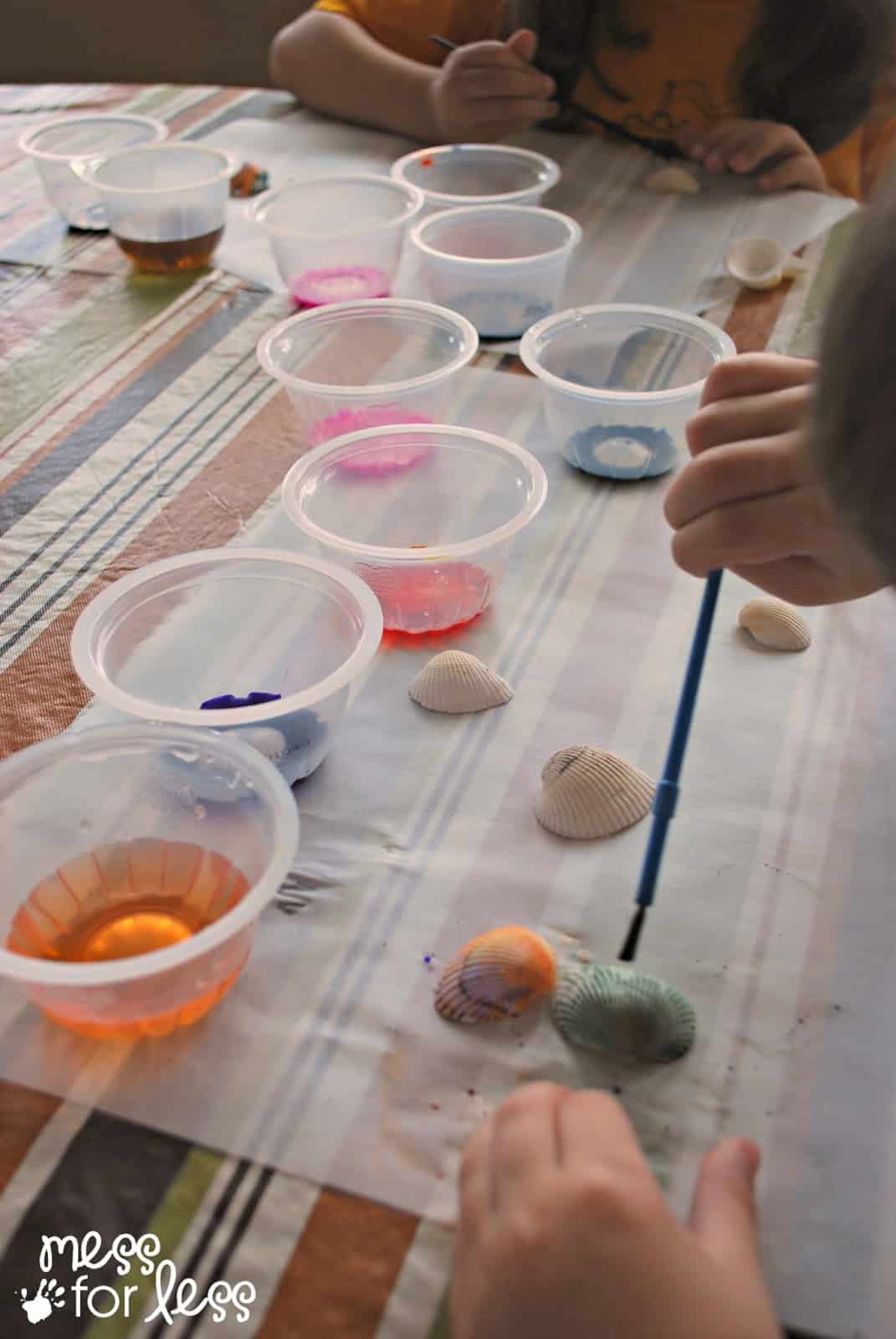 child painting shells with watercolor paint