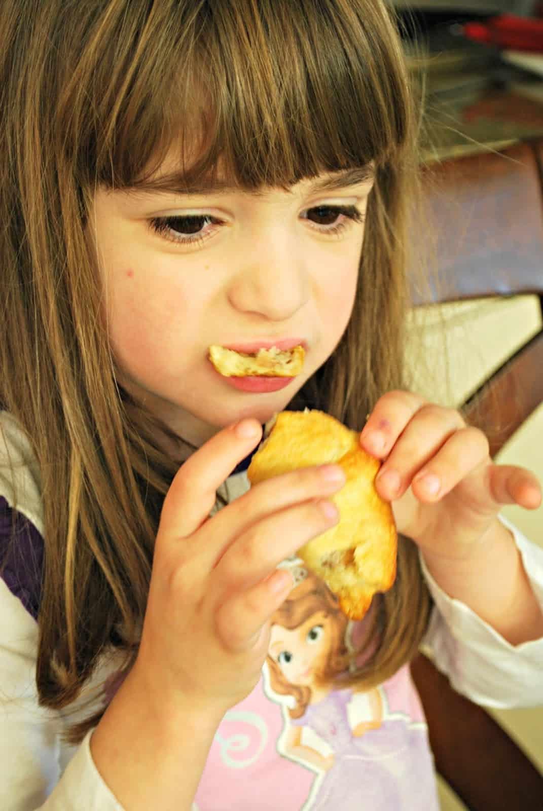 child eating crescent rolls