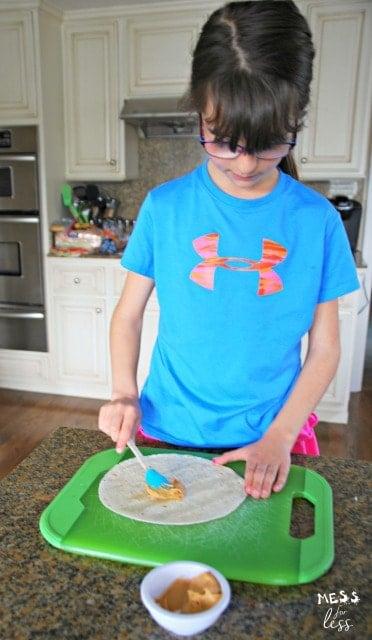 spreading peanut butter on a tortilla