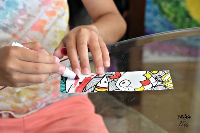 child coloring a bookmark with markers