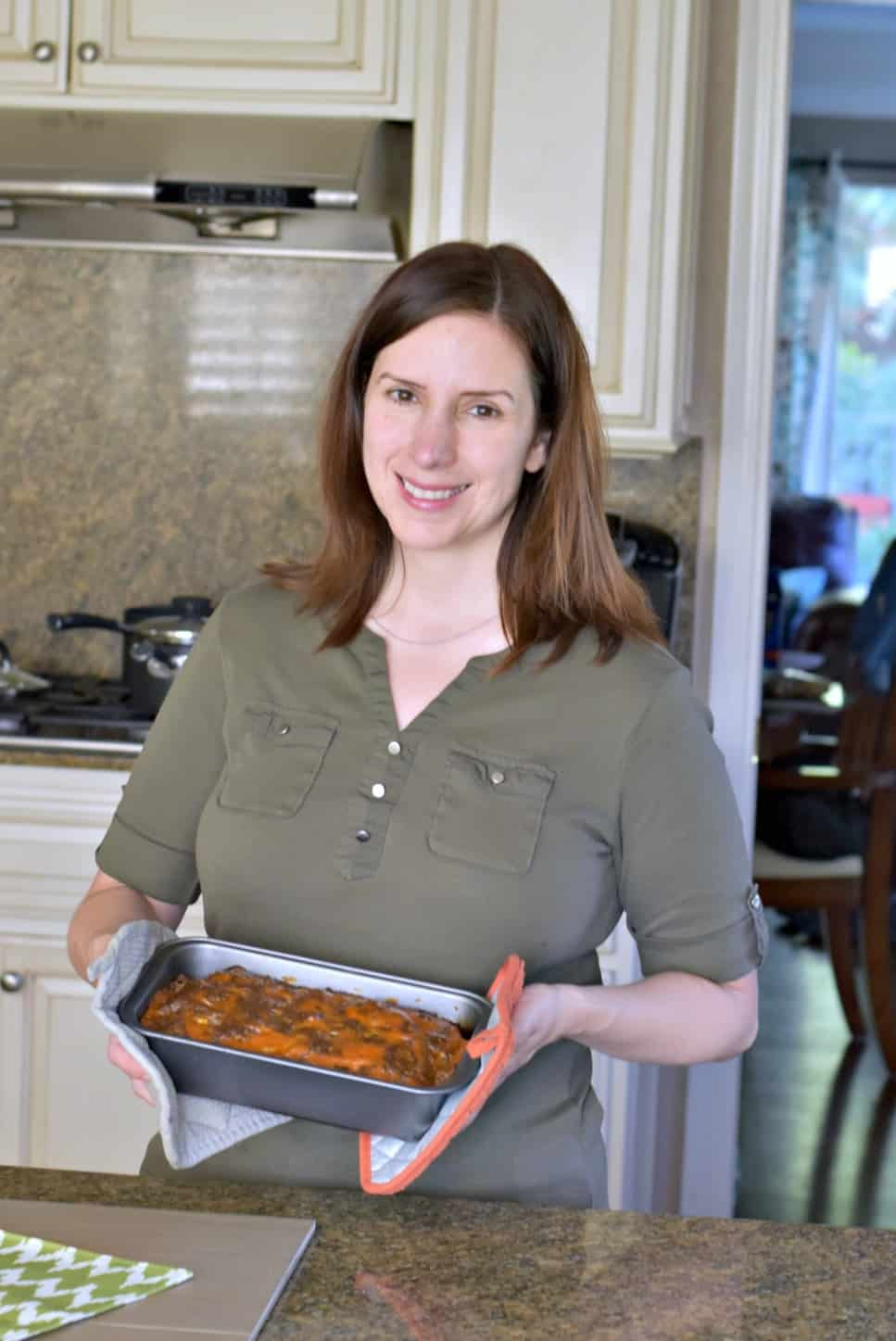 woman holding meatloaf in a pan