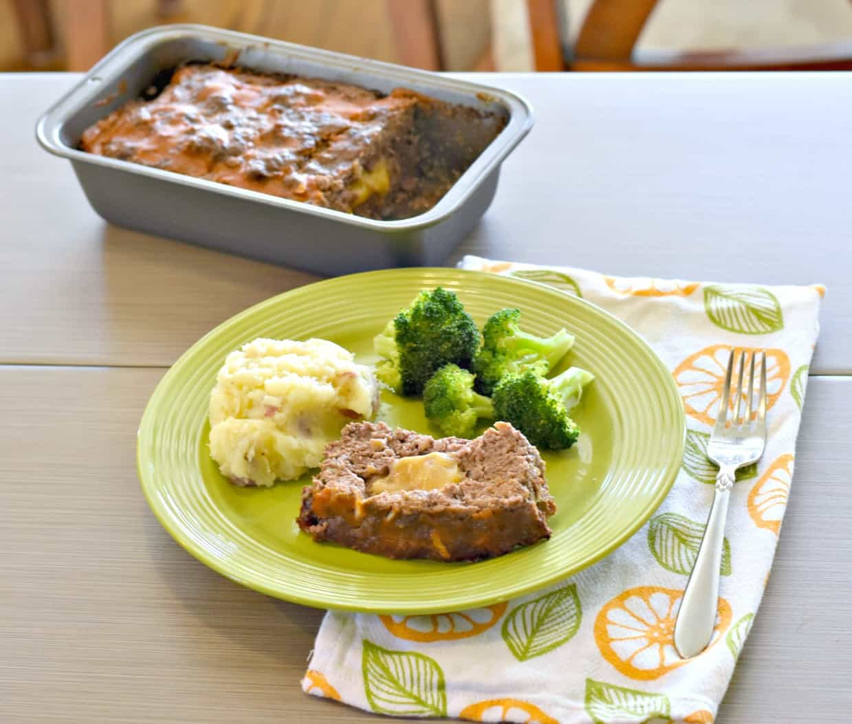 slice of cheeseburger meatloaf with mashed potatoes and broccoli