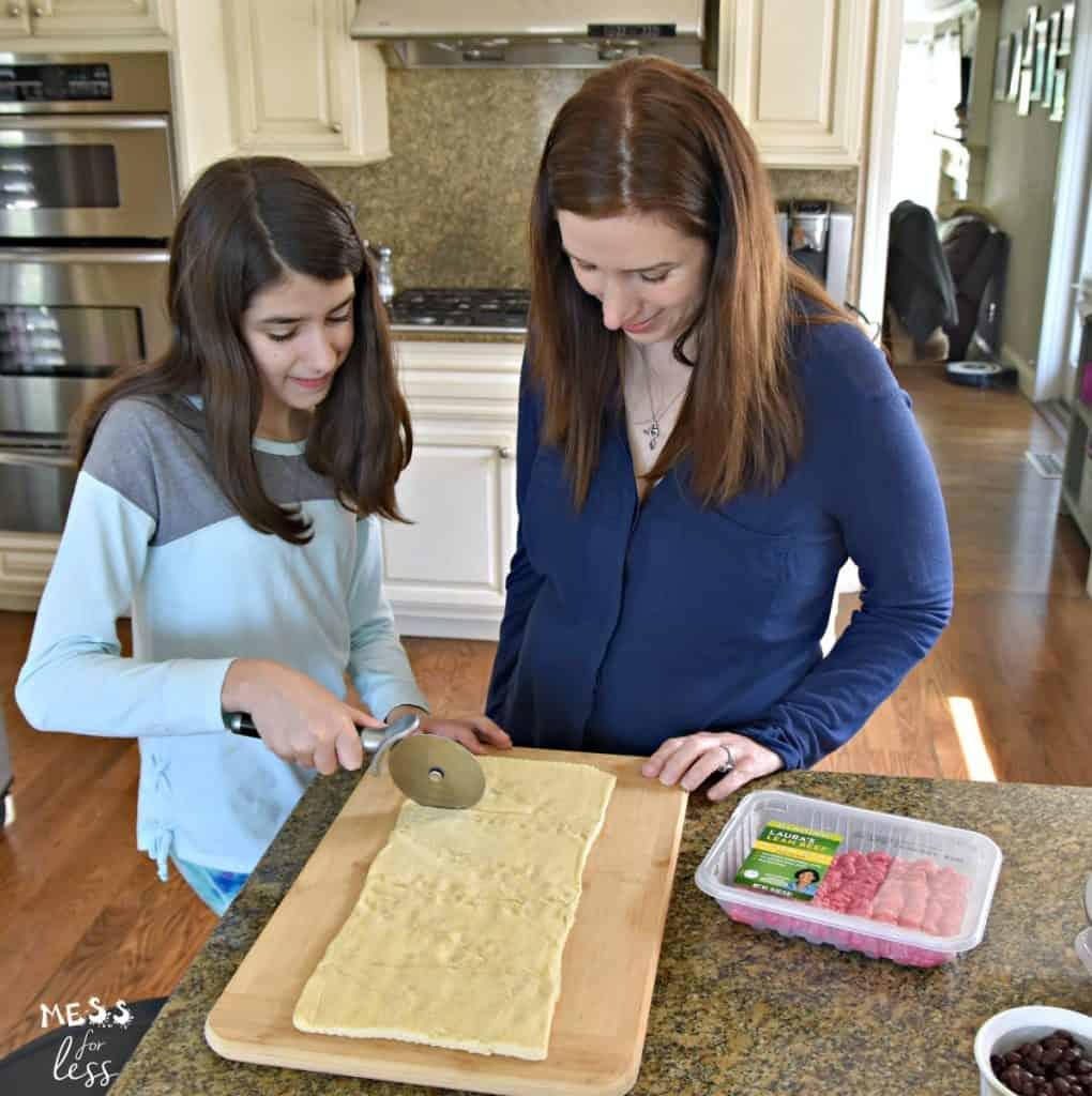child slicing crescent roll dough
