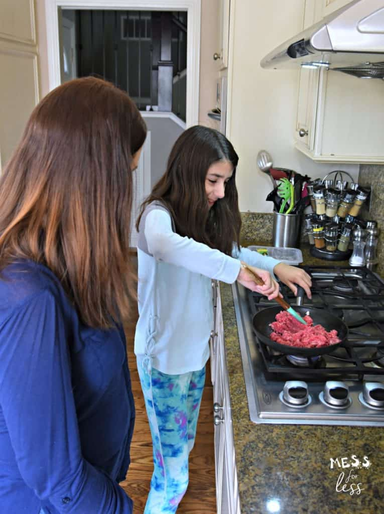 family cooking beef in a skillet