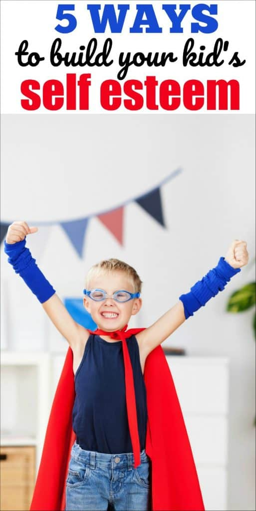 boy dressed as superhero with arms raised in the air