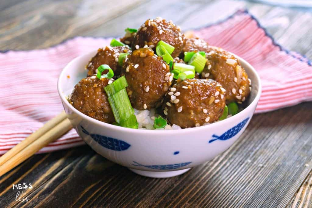 glazed meatballs over rice in a while bowl