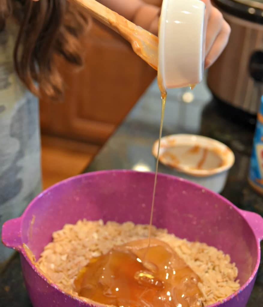pouring honey into a bowl with rice krispies peanut butter and oats