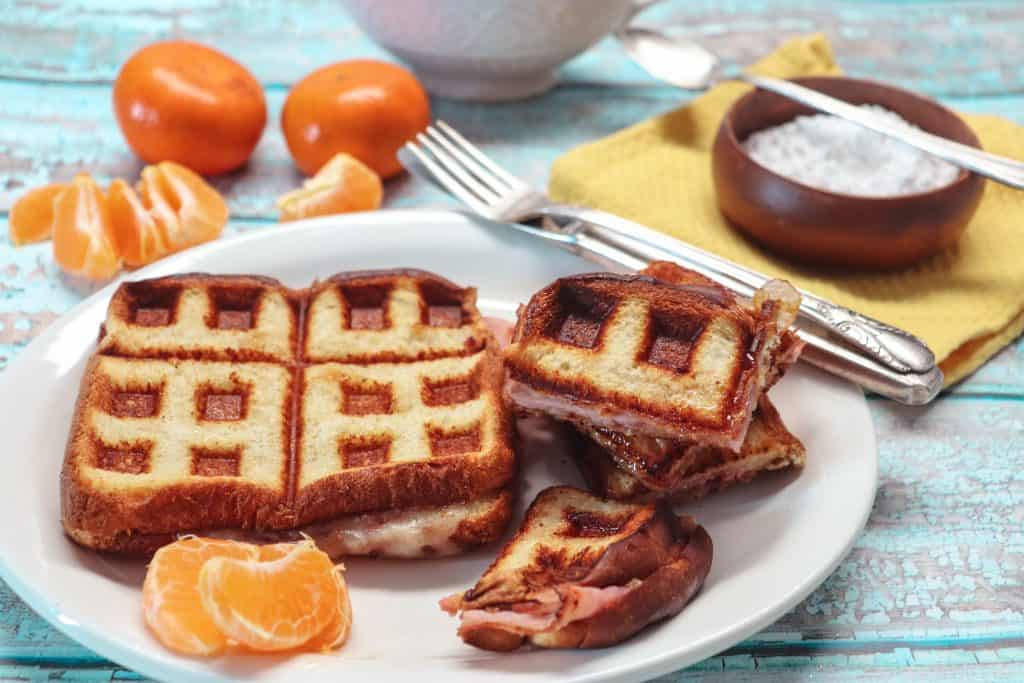 monte cristo sandwich on a plate with oranges