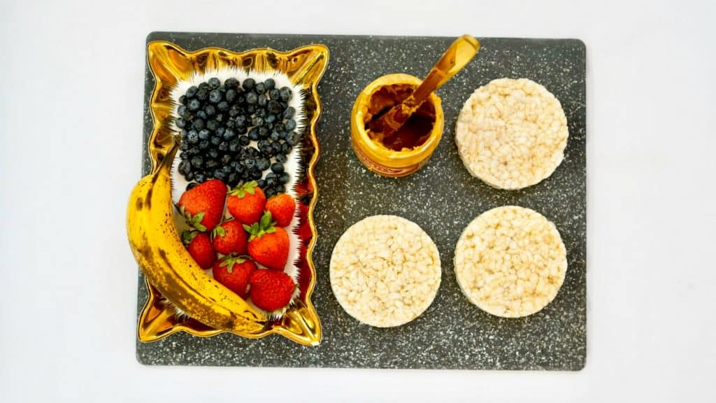 rice cakes and peanut butter and fruit on a cutting board