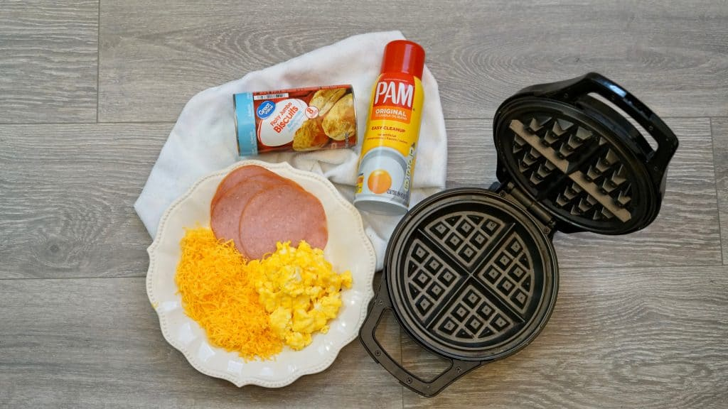 eggs cheese ham on a plate and a waffle maker