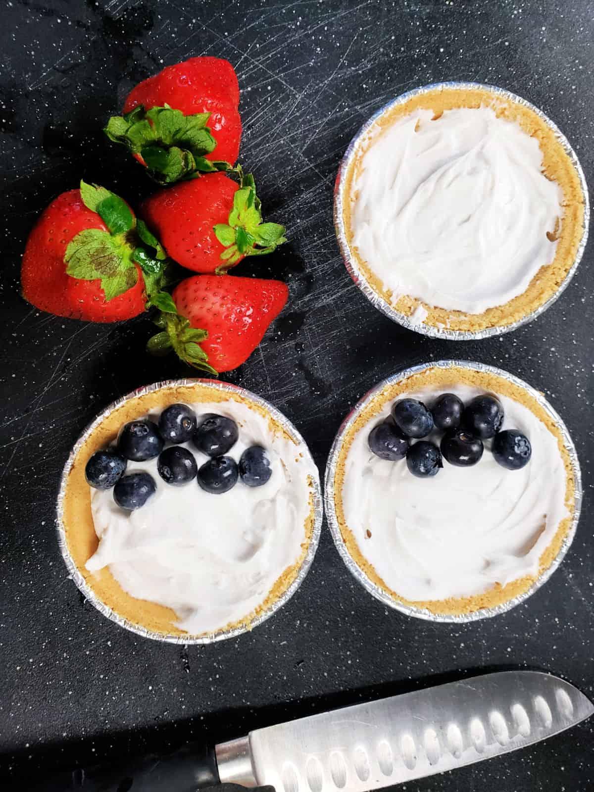 strawberries on a cutting board and coconut cream pies with blueberries