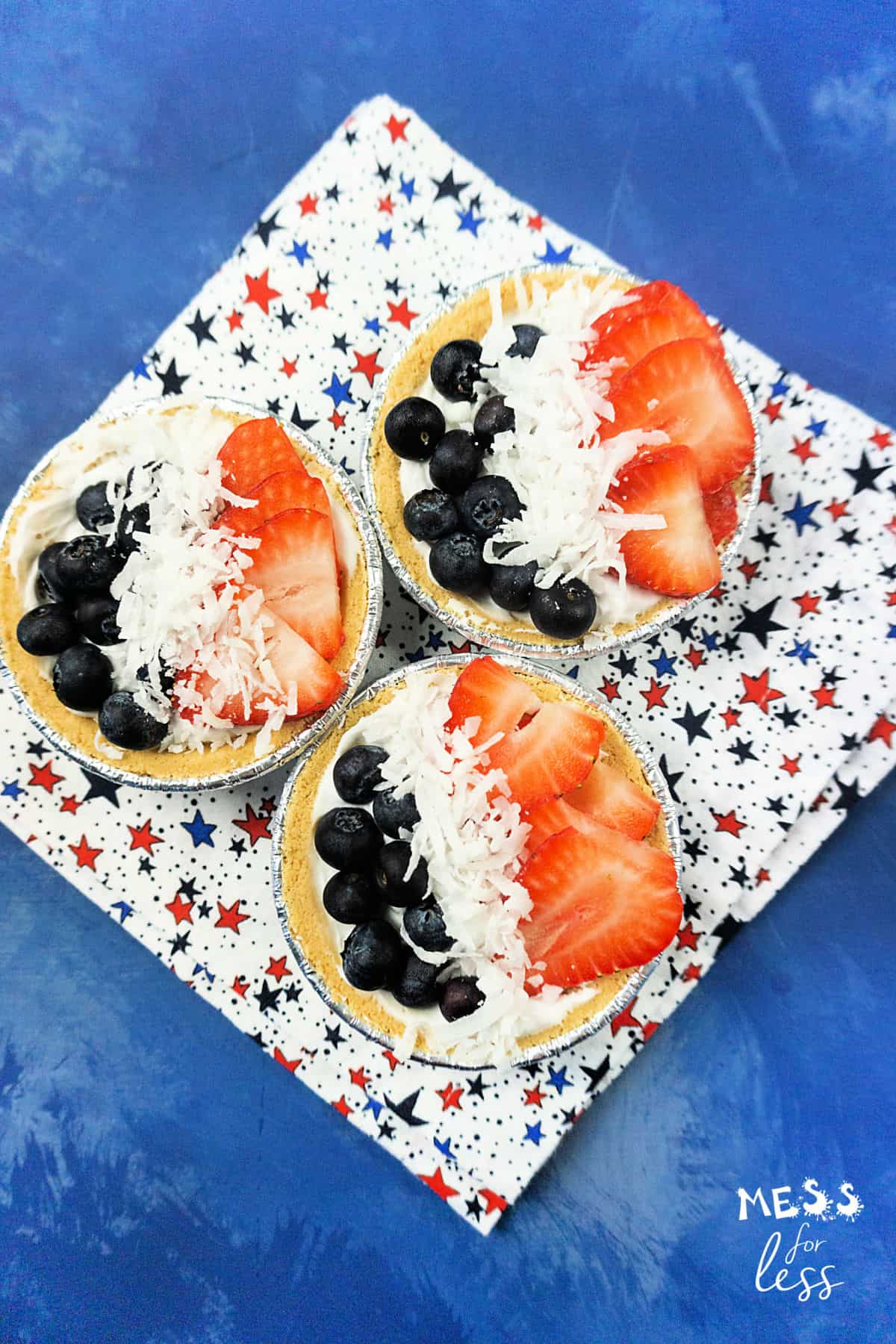 blueberry and strawberry mini cream pies on a star background