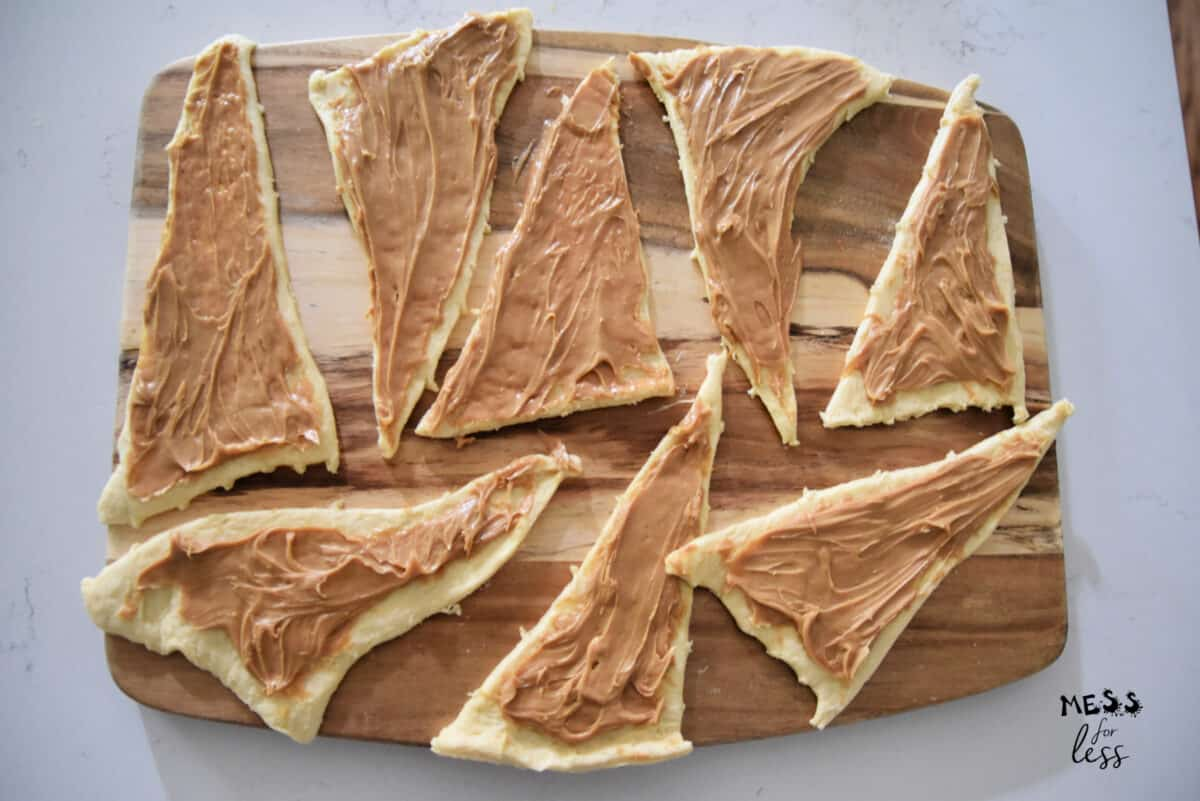 crescent rolls on a cutting board with peanut butter