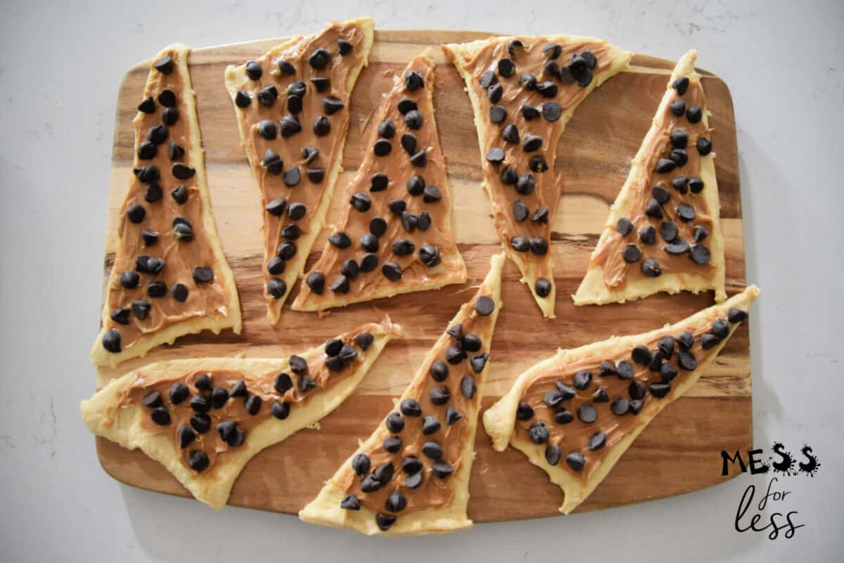 crescent rolls with peanut butter and chocolate chips on a cutting board