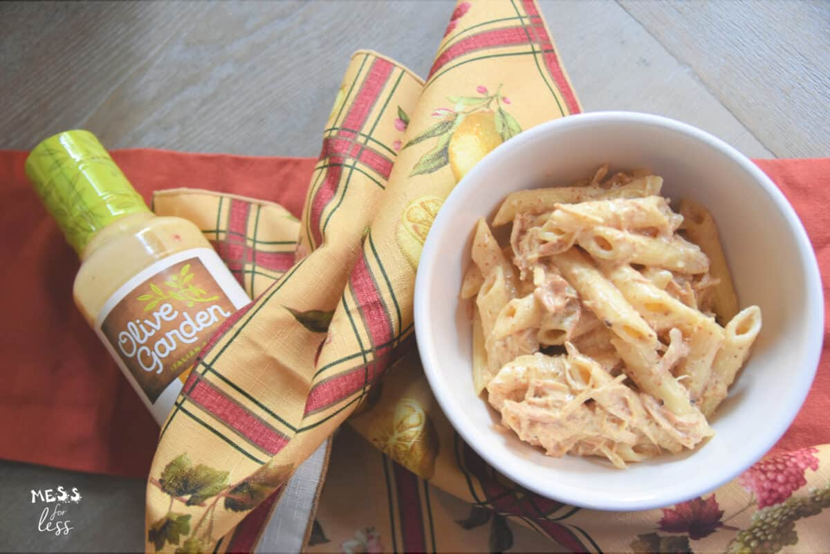 olive garden pasta and chicken in a bowl and a bottle of olive garden dressing