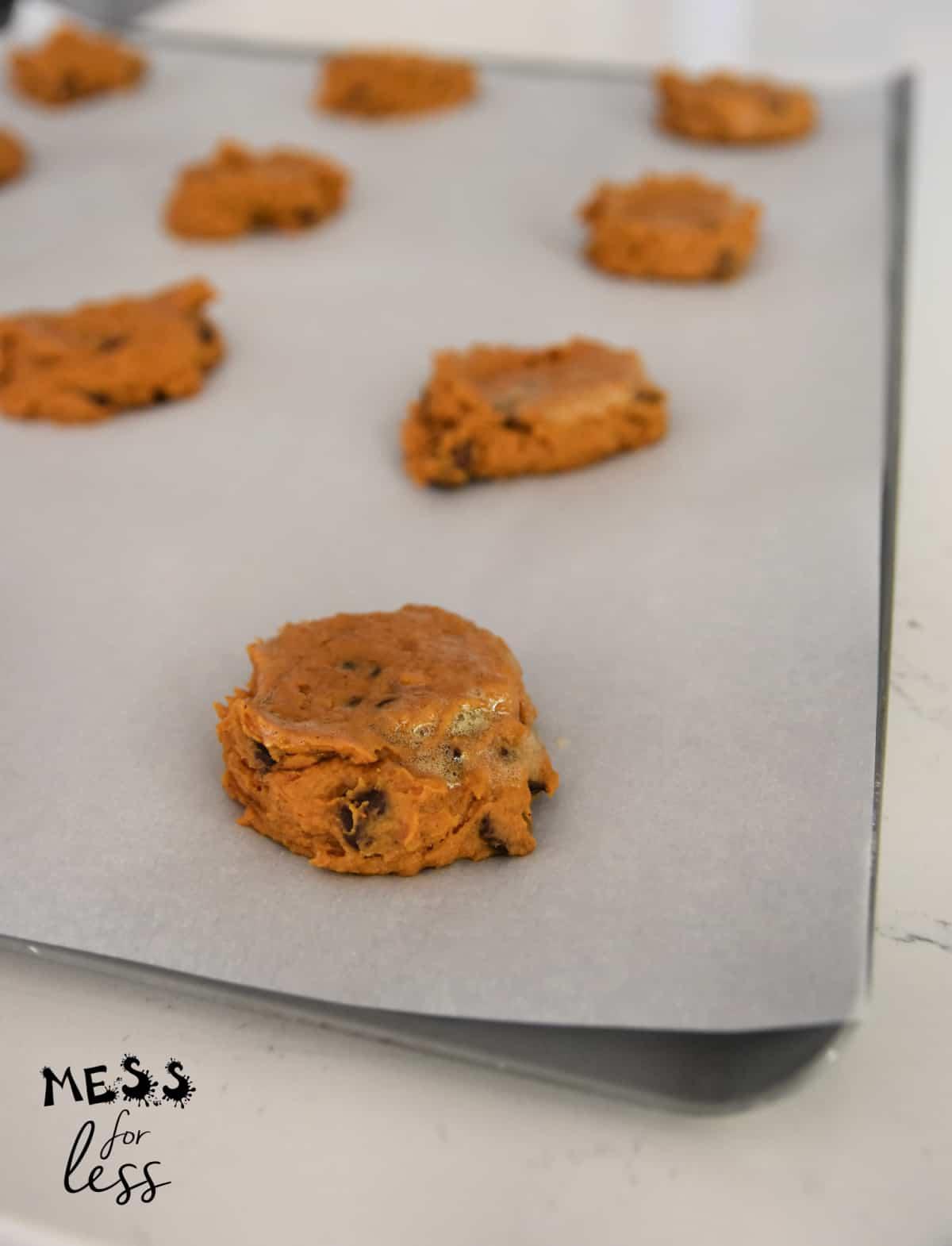 pumpkin chocolate chip cookies on a cookie sheet